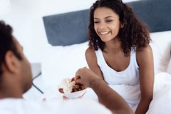 Black men and women sit in their bed in the morning in the bedroom. A man is feeding a woman a strawberry with cream. Royalty Free Stock Photography