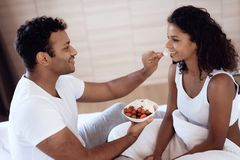 Black men and women sit in their bed in the morning in the bedroom. A man is feeding a woman a strawberry with cream. Stock Photos