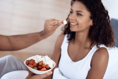 Black men and women sit in their bed in the morning in the bedroom. A man is feeding a woman a strawberry with cream. Stock Photo