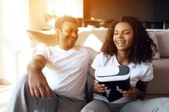 Black man and woman are sitting on the couch. A man and a woman hold a helmet of vr in their hands and dispose of it. Black men and women are sitting on the Royalty Free Stock Image