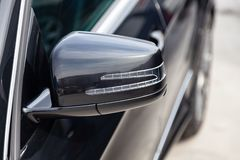 Black Mercedes Benz E-class E250 2010 year front side mirror view with dark gray interior in excellent condition in a parking royalty free stock photo