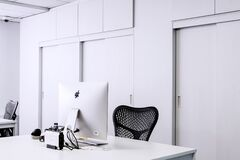 Black Mesh Office Rolling Chair Beside White Wooden Desk With White Imac Royalty Free Stock Image