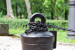 A black metal chain with large links chained to a heavy concrete pedestal. decorative fence in the park. A black metal chain with large links chained to a heavy royalty free stock images