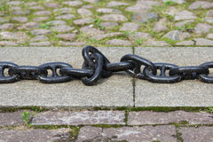 A black metal chain with large links lies on concrete slabs on the ground. A black metal chain with large links lies on concrete slabs on the ground stock photography
