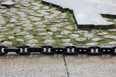 A black metal chain with large links lies on concrete slabs on the ground. A black metal chain with large links lies on concrete slabs on the ground royalty free stock images