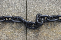 A black metal chain with large links lies on concrete slabs on the ground. A black metal chain with large links lies on concrete slabs on the ground royalty free stock photo