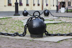 Black metal chain with large links and round heavy weights lies on concrete slabs on the ground. Black metal chain with large links and round heavy weights lies royalty free stock image