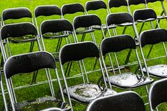 Black metal chairs stand outside in the park in the rain. Empty auditorium, green grass, waterdrops, closeup stock photo