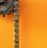 Black metal cogwheel and chain on orange background with empty space. Stock Photo
