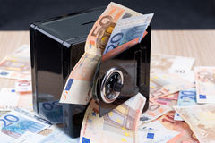 Black metal coin bank with money Royalty Free Stock Images