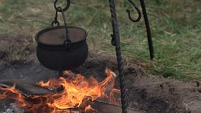 Black metal cooking pot over fire at the camp site outdoors. Preparing food outside on a camp fire.  stock video footage