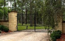 Black metal driveway entrance gates set in brick fence. Black wrought iron metal driveway entrance gates set in brick fence Stock Image