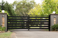 Black metal driveway entrance gates set in fence Stock Photos