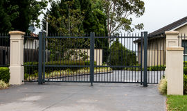 Black metal driveway entrance gates set in fence Stock Photo