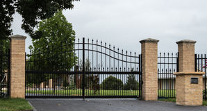 Black metal driveway entrance gates set in fence. Black wrought iron driveway entrance gates set in brick fence with garden background Royalty Free Stock Images