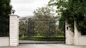 Black metal driveway entrance gates set in fence. Black wrought iron driveway entrance gates set in white brick fence with trees Royalty Free Stock Photography
