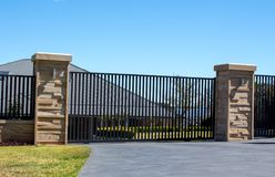 Free Black Metal Driveway Entrance Gates Set In Sandstone Brick Fence With Residential Garden Stock Image - 100039711