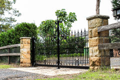 Black metal entrance gates set in sandstone fence. Black wrought iron driveway entrance gates set in sandstone brick fence Stock Photo