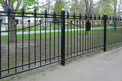 Black metal fence. Outdoors. Spring day Royalty Free Stock Photo