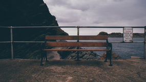 Black Metal Frame Brown Wooden Bench Beside Black Metal Fence during Twilight Royalty Free Stock Photos