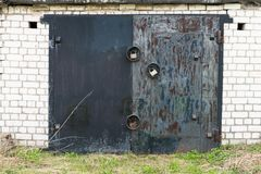Black metal garage gate with three big locks Stock Photo