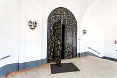 Black metal gate with decorative iron patterns golden colors. Raifa, Kazan, Russia - June 10, 2018: Black metal gate with decorative iron patterns golden colors stock images