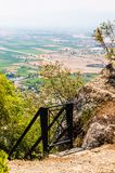 Black metal gate, railings and stairs down the hill from Meteora rock formations cliffs with scenic view on the valley full of. Black metal gate, railings and stock images
