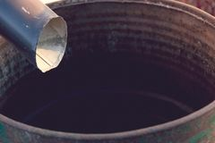 Black metal gutter downspout draining into rain barrel on sunny. Day in garden. Matte effect stock photography