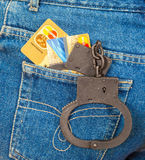Black metal handcuffs and credit cards in back jeans pocket Royalty Free Stock Photos