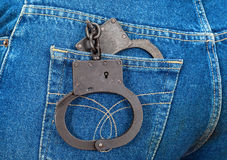 Black metal handcuffs in jeans pocket Stock Photo
