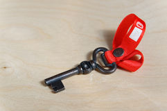 Black metal key figure with red ribbon Royalty Free Stock Photo
