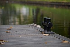 Black metal mooring bollard on a wooden pier at a lake, copy space, detail with selected focus and narrow depth of field Royalty Free Stock Image