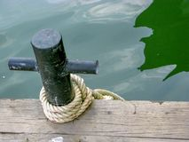 Black metal mooring rope with white rope on wooden pier found on an island. royalty free stock images