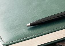 Black metal pen on a leather notepad close up. With copy space Royalty Free Stock Images