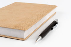 Black metal pen next to diary beige color Stock Photo