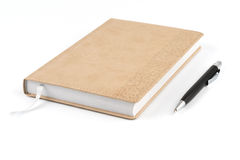 Black metal pen next to diary beige color Royalty Free Stock Images