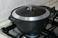 Black metal pot covered with a lid on the gas stove Stock Photo