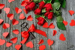Black Metal Skeleton Key Beside Red Roses Bouquet on Gray Surface royalty free stock photography