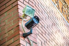 Black metal street security video camera on wall royalty free stock photo