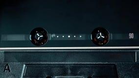Black metal top grade audio cassette spinning, clean close-up. Vintage top class audio cassette spinning in the deck, clean close-up stock video