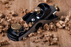 Black metal wood planer and shavings. On wooden plank Royalty Free Stock Image