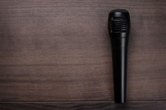 Black mic on the wooden table. Black mic on the brown wooden table Stock Image