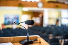 Black microphone in an empty conference hall, empty chair, ready for public speaking. Black microphone in an empty conference hall, empty chair, ready for royalty free stock photo