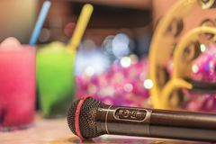 Black microphone in karaoke club, with remote controller, melon stock images