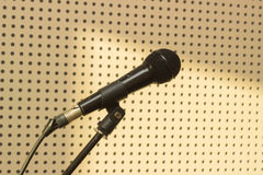 Black microphone in the studio for practicing vocals. Black microphone on the background wall in the studio for practicing vocals Royalty Free Stock Photos