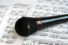 A black microphone on the top of music sheets Royalty Free Stock Images