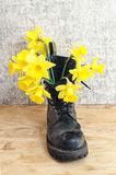 Black military muddy shoes with yellow narcissus Stock Photo