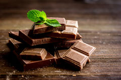 Black and milk chocolate bars with mint dark wooden table background. Black and milk chocolate bars with mint on dark wooden table background Royalty Free Stock Images