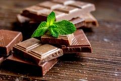 Black and milk chocolate bars with mint dark wooden table background. Black and milk chocolate bars with mint on dark wooden table background Royalty Free Stock Photo