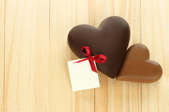 Black and milk chocolate hearts on wooden background Royalty Free Stock Photos